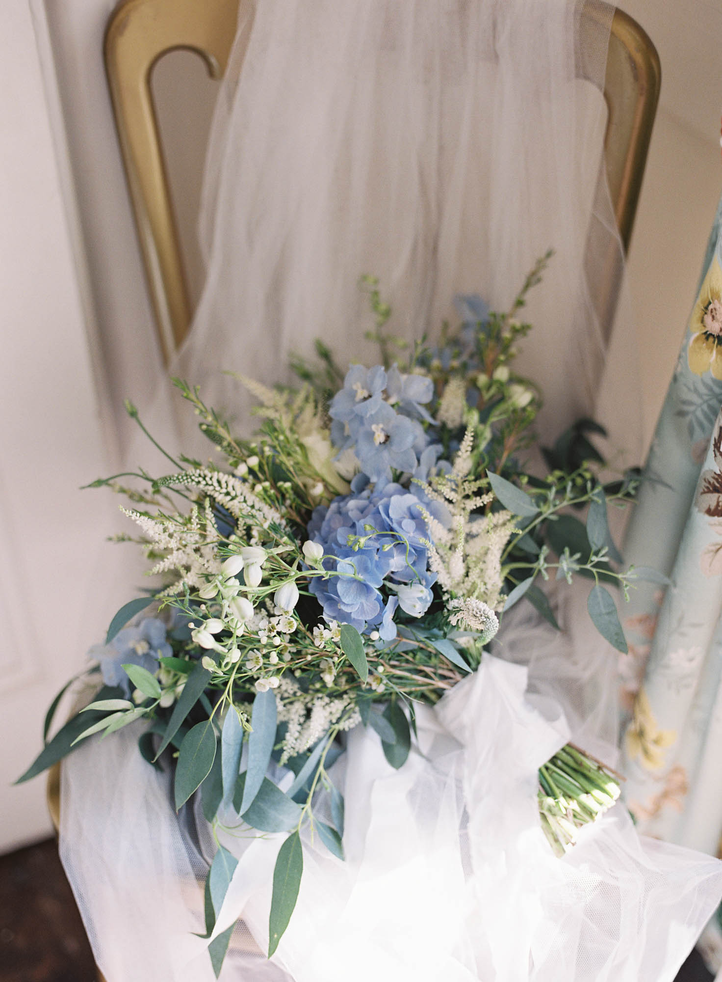 Bridal wedding bouquet in blue, white and green on chair with veil