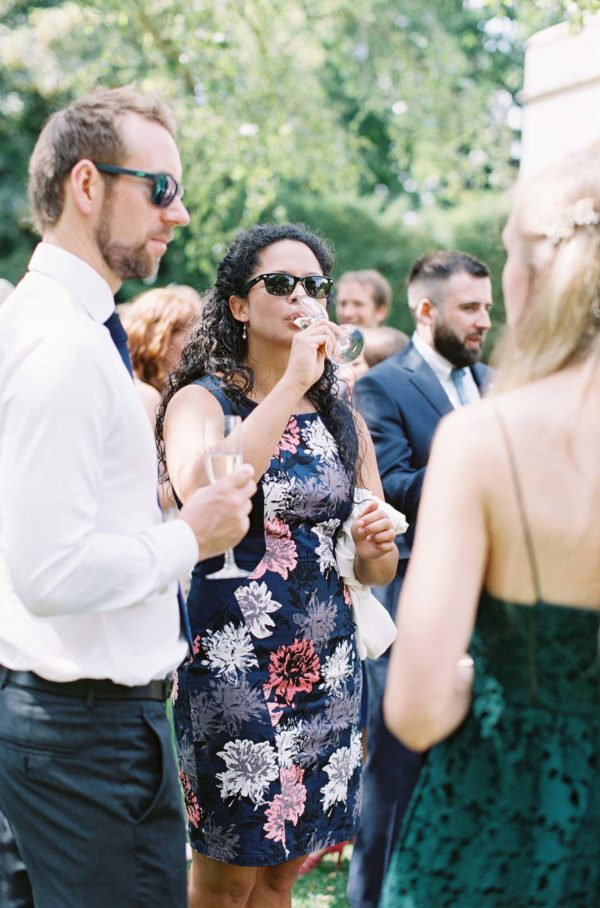 wedding guest drinking champagne at Chiddingstone Castle wedding