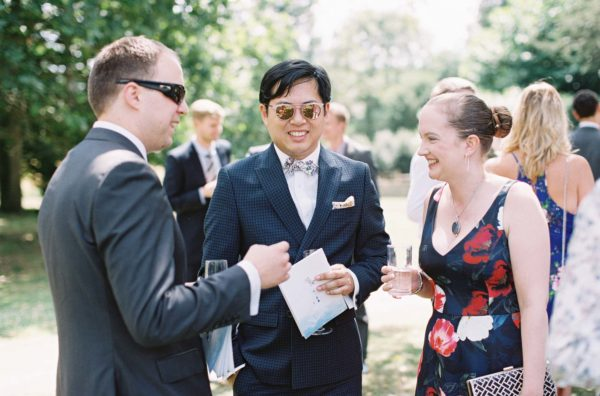 Wedding guests talking and laughing at Chiddingstone Castle