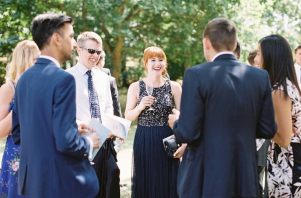Guests laughing and talking during reception at Chiddingstone Castle wedding