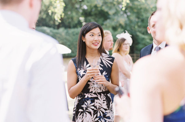 Female wedding guest holding champagne and smiling at Chiddingstone Castle wedding