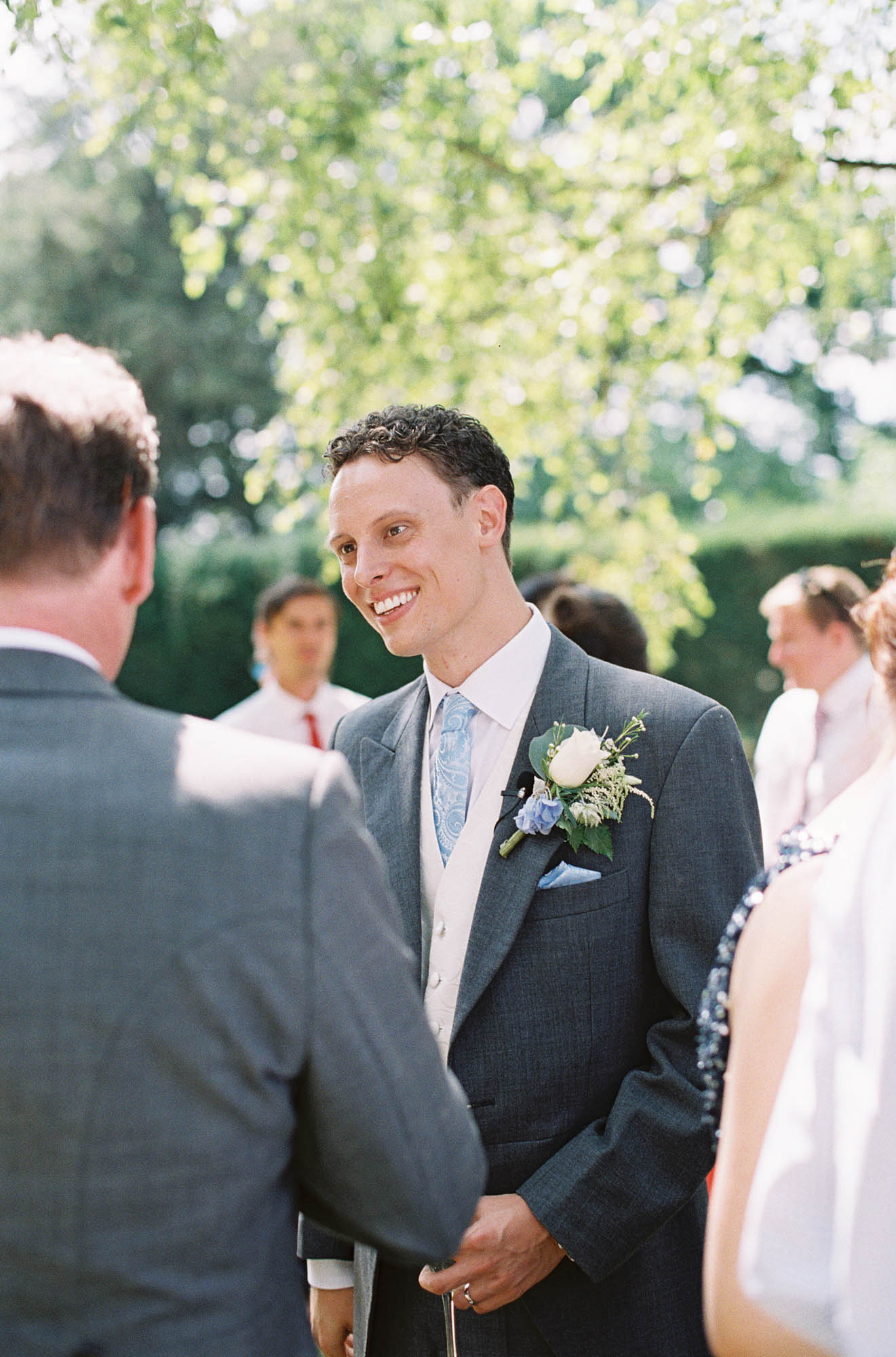Groom talking and smiling at Chiddingstone Castle wedding