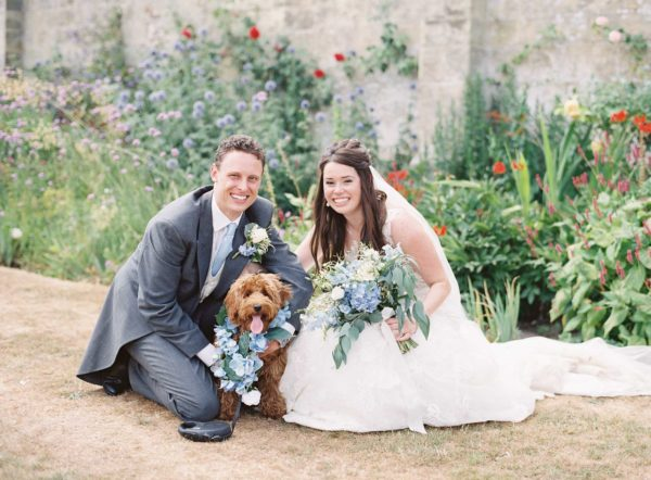 Bride and groom with their dog wearing a floral garland around it's neck