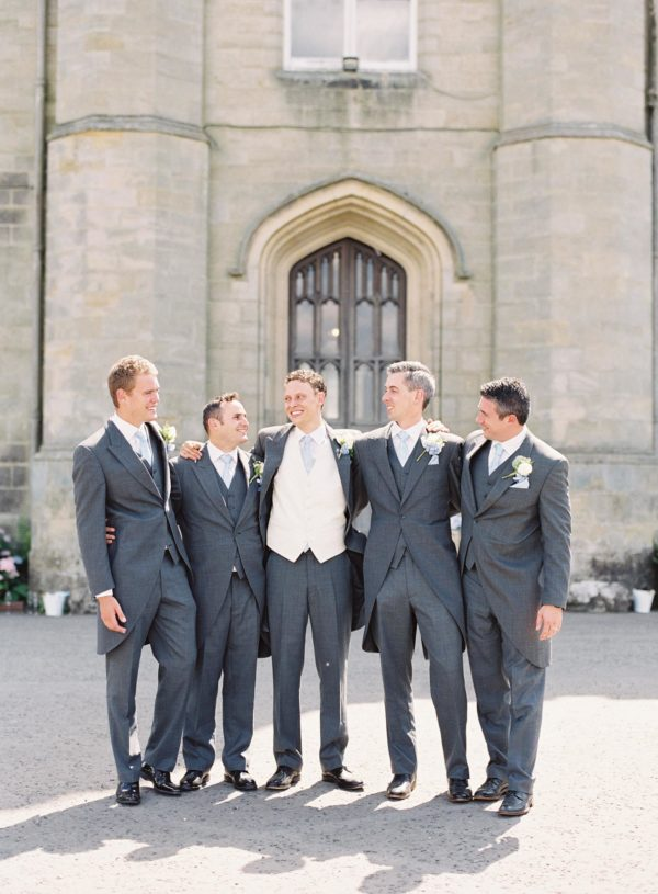 Groom with groomsmen laughing at Chiddingstone Castle wedding