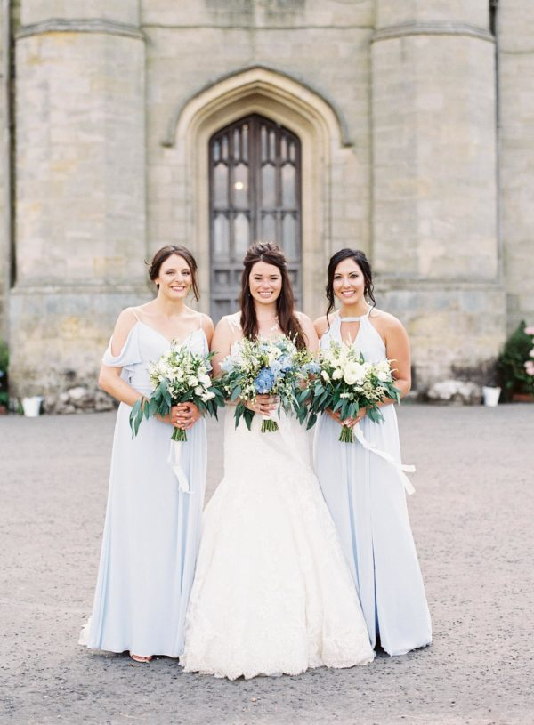 Bride with bridesmaids in blue dresses holing bouquets at Chiddingstone Castle wedding