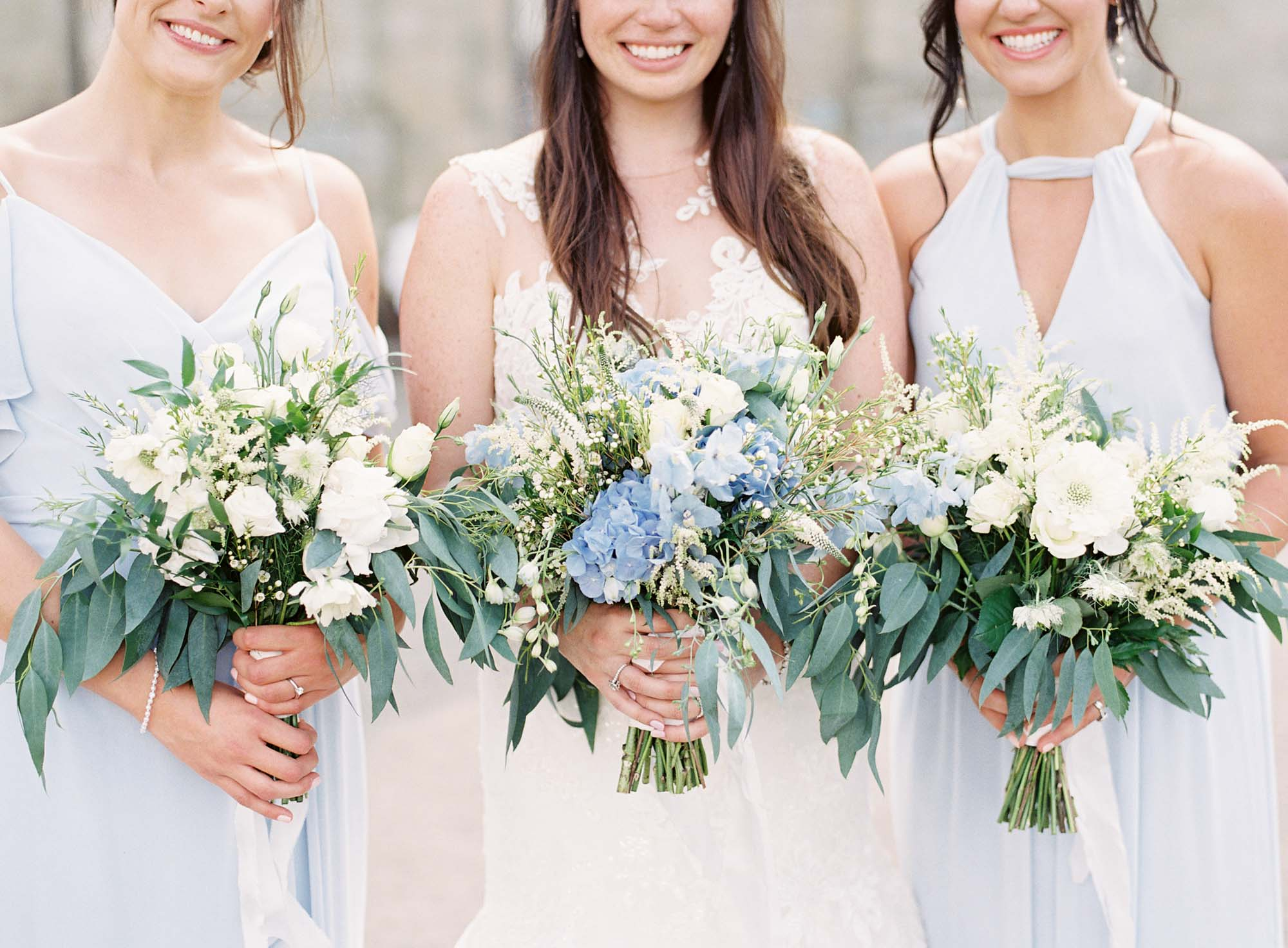 White, blue and green wedding bouquets being held by bride and bridesmaids