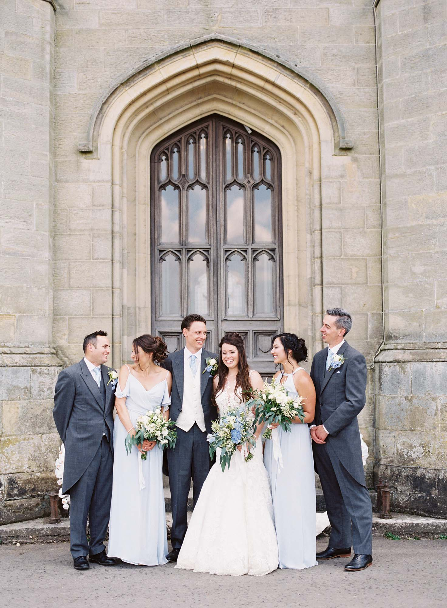 Bridal party laughing in natural wedding photography at Chiddingstone Castle wedding