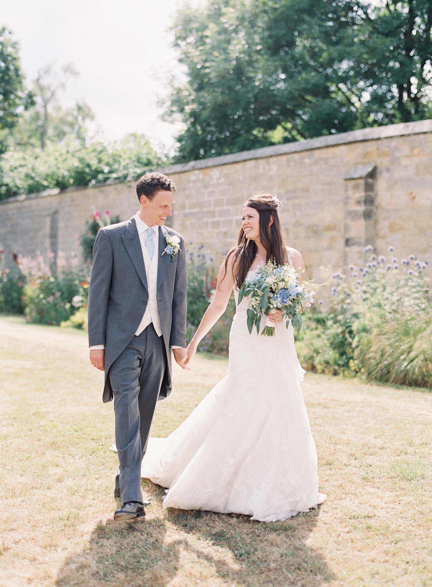 Bride and groom talking and walking hand in hand at Chiddingstone Castle wedding
