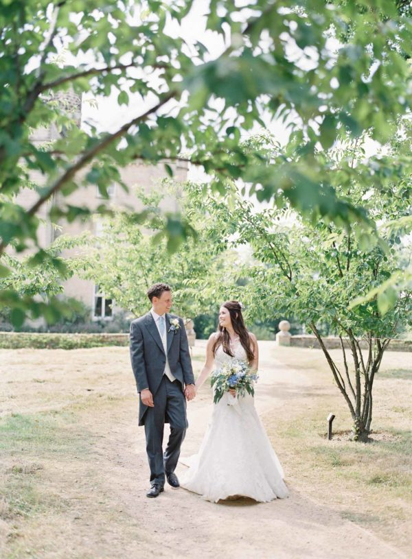 Bride and groom walking in the grounds of Chiddingstone Castle under trees