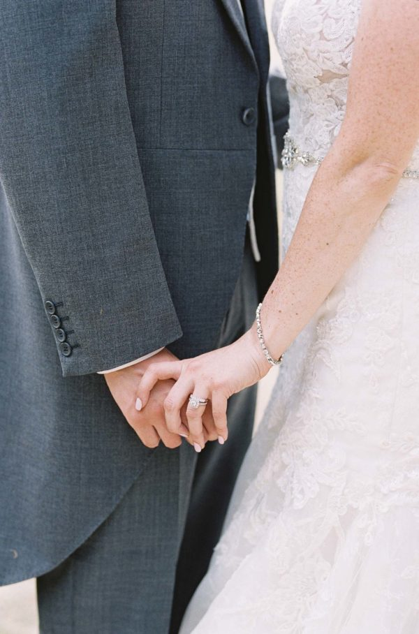 Bride and groom holding hands at Chiddingstone Castle wedding