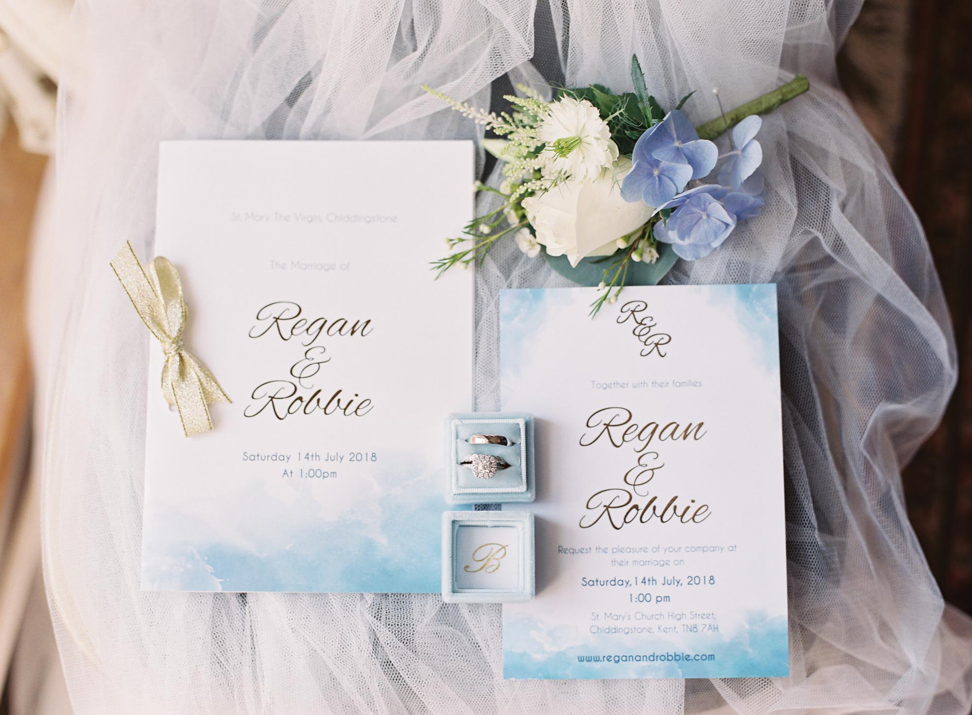Blue, white and gold wedding stationery with engagement ring and wedding ring