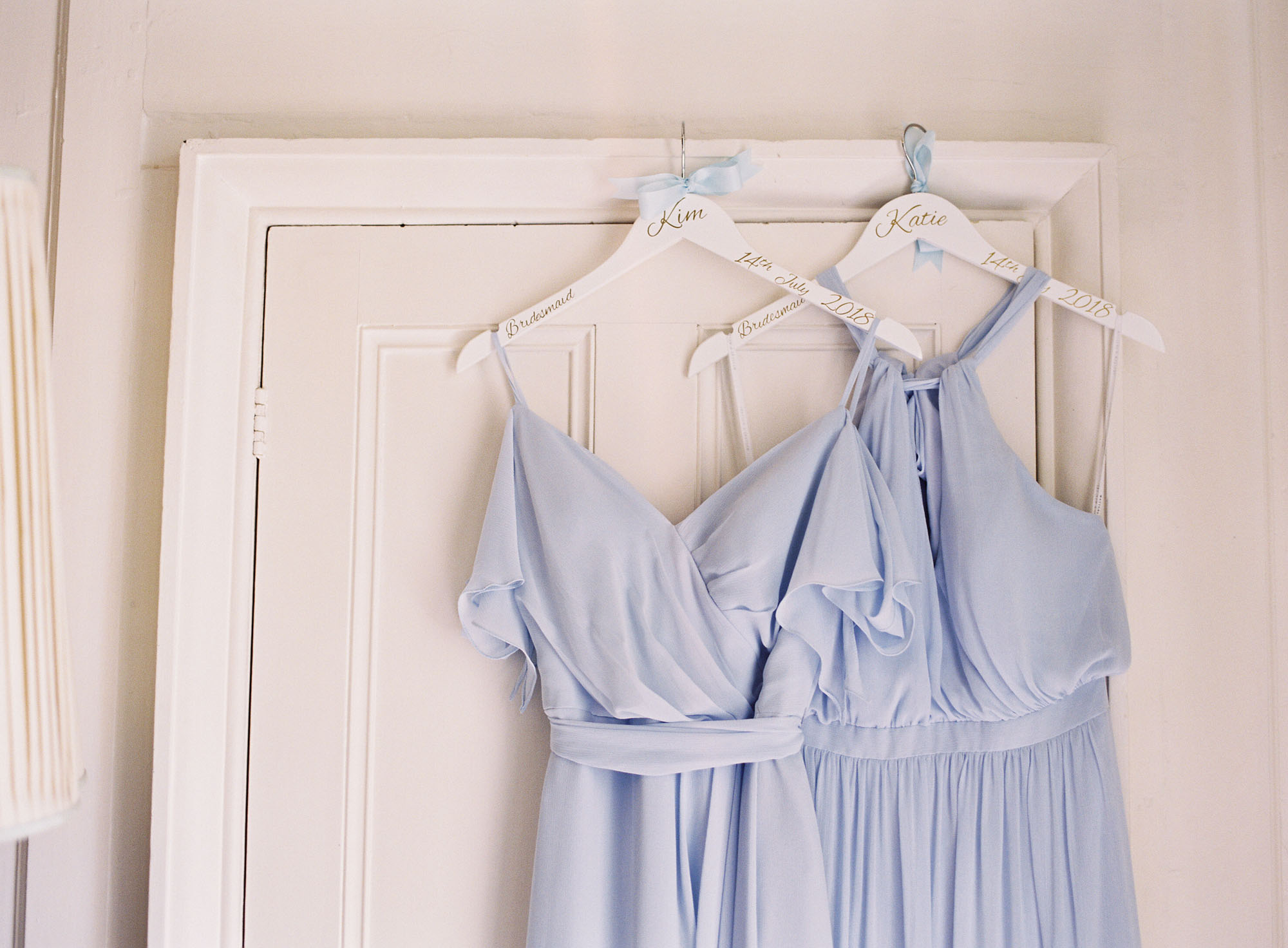 Blue chiffon bridesmaids dresses hanging on doorframe at Chiddingstone Castle