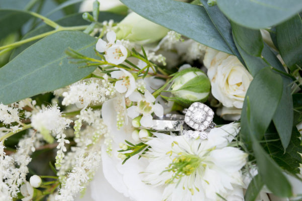 Bride and grooms diamond engagement and wedding rings in flowers
