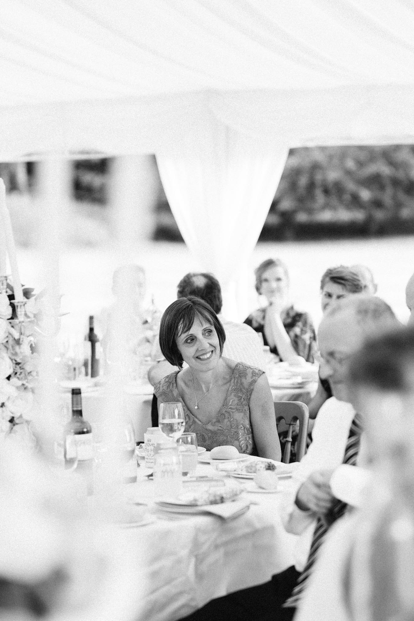 Mother of the groom smiling during speeches in black and white photograph