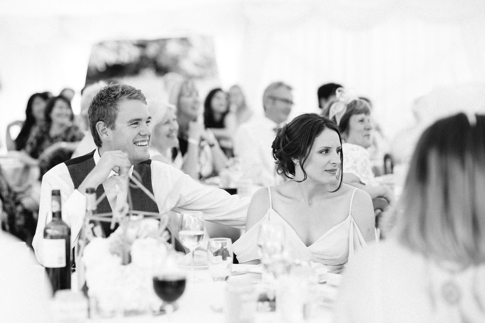 Black and white photograph of guests enjoying speeches at Chiddingstone Castle wedding