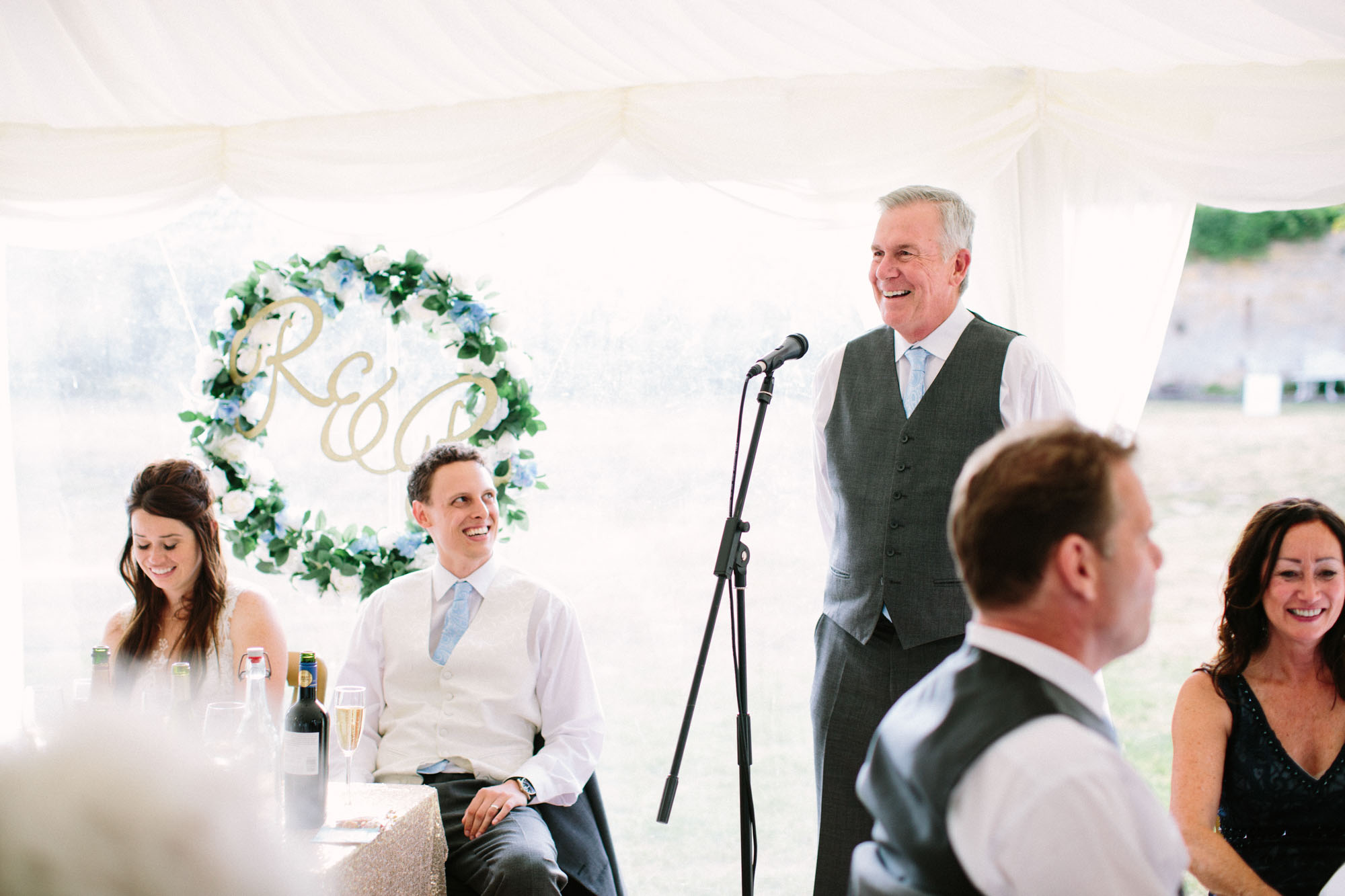 Father of the bride giving speech and bride and groom laughing