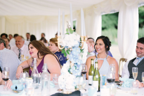 Wedding guests smiling and laughing during speeches at Chiddingstone Castle
