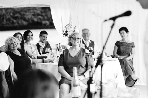Black and white photograph of guests enjoying the speeches at marquee at Chiddingstone Castle