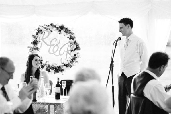 Bride and groom smiling at eachother during speeches at Chiddingstone Castle wedding
