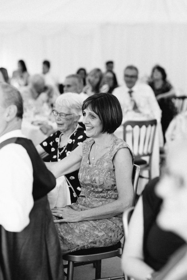 Mother of the groom smiling during wedding speeches at Chiddingstone Castle
