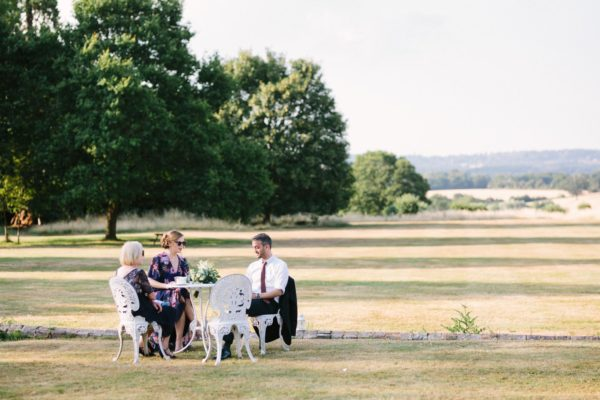Guests sitting outside enjoying the evening sunshine at Chiddingstone Castle wedding