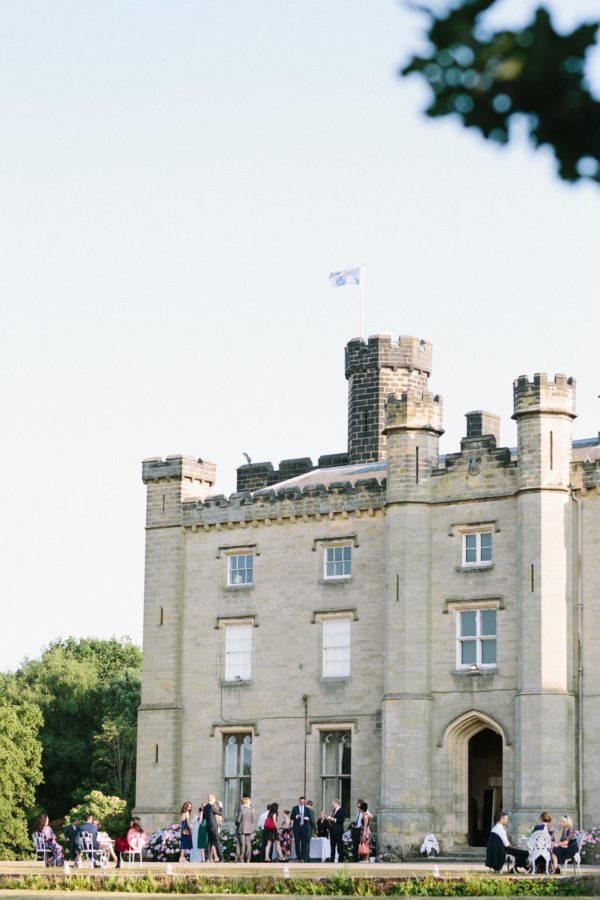 Flag flying and guests mingling outside at Chiddingstone Castle wedding