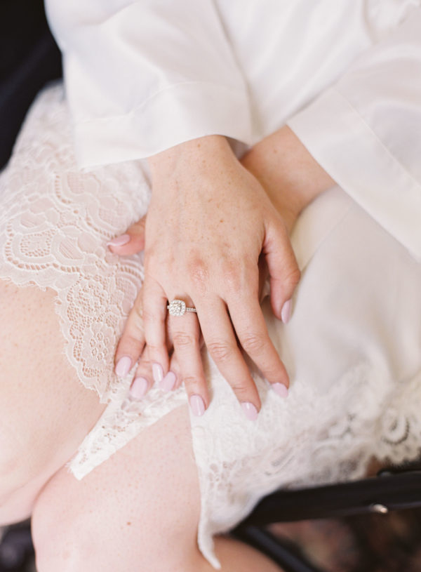 Brides hands with engagement ring on and white silk dressing gown