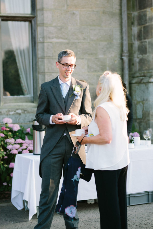 guests smiling and drinking tea outside Chiddingstone Castle