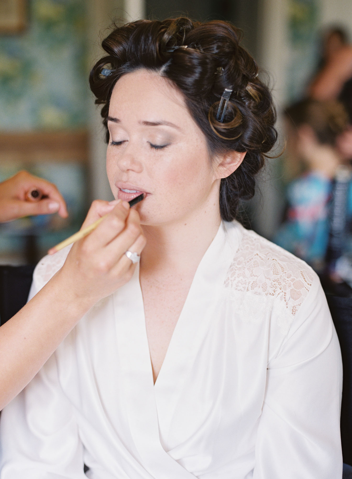 Bride having her make up done on wedding morning at Chiddingstone Castle