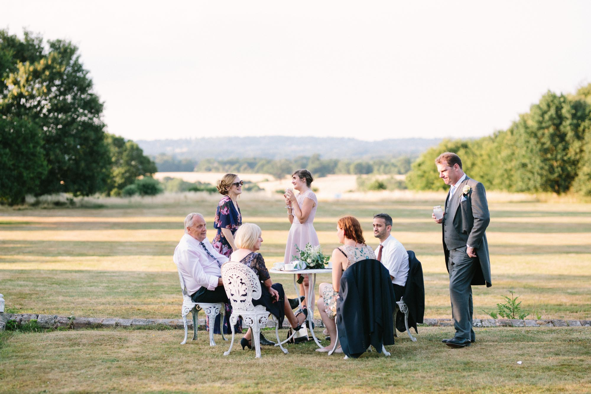 Guests sitting on garden furniture outside Chiddingstone Castle wedding