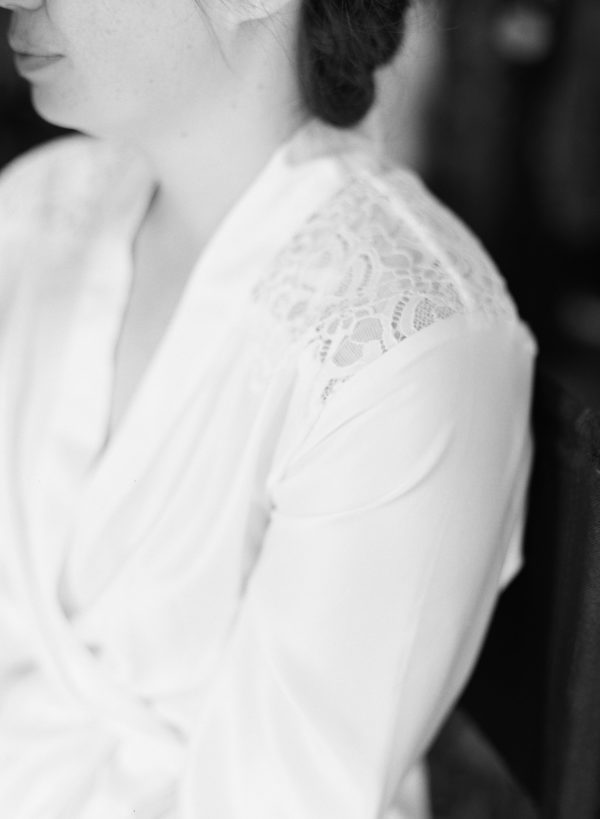 Black and white lace detailing on shoulder of brides dressing gown