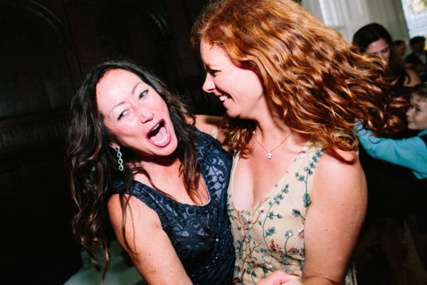 Two women dancing and singing at a Chiddingstone Castle wedding