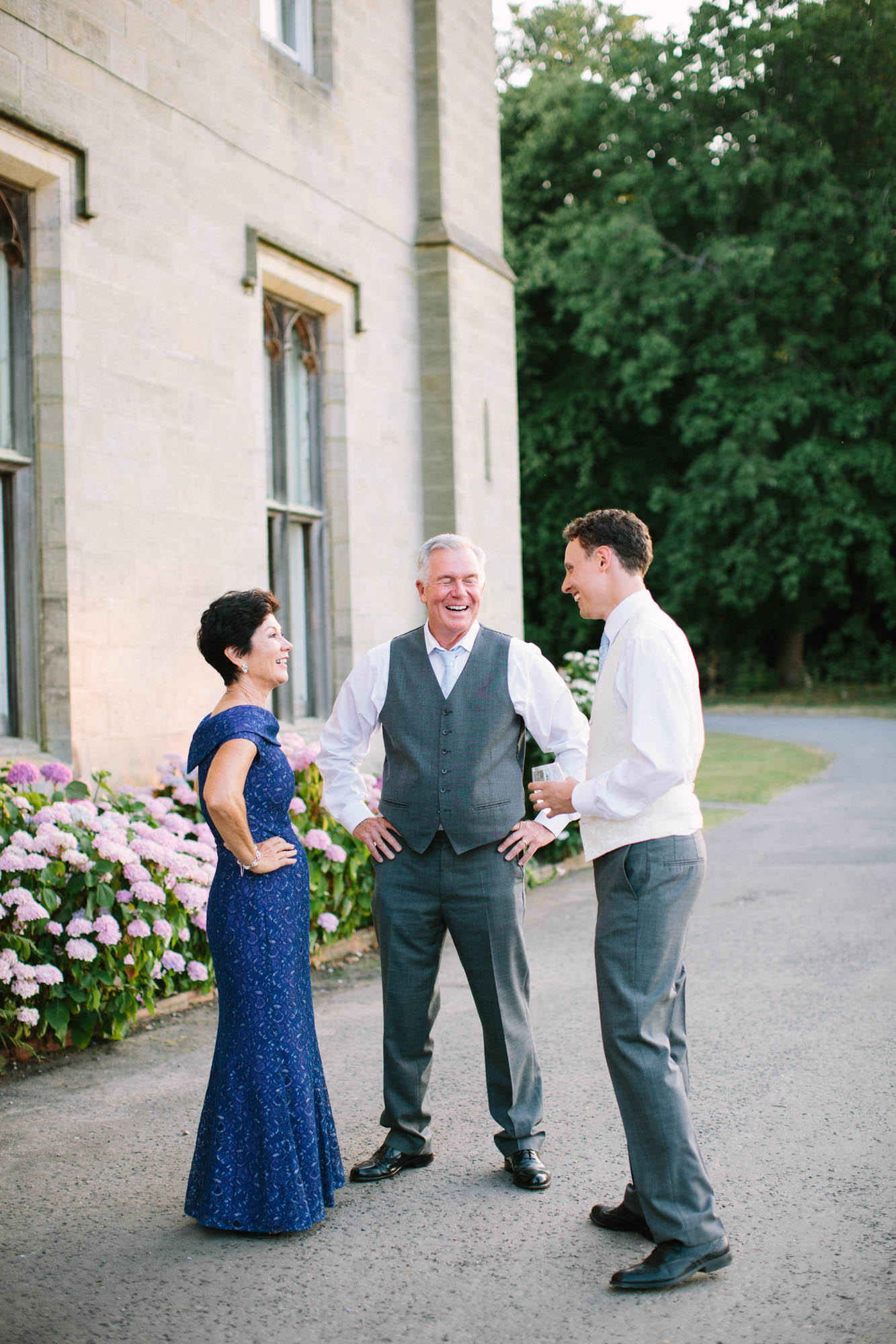 Groom chatting to bride's parents outside Chiddingstone Castle wedding