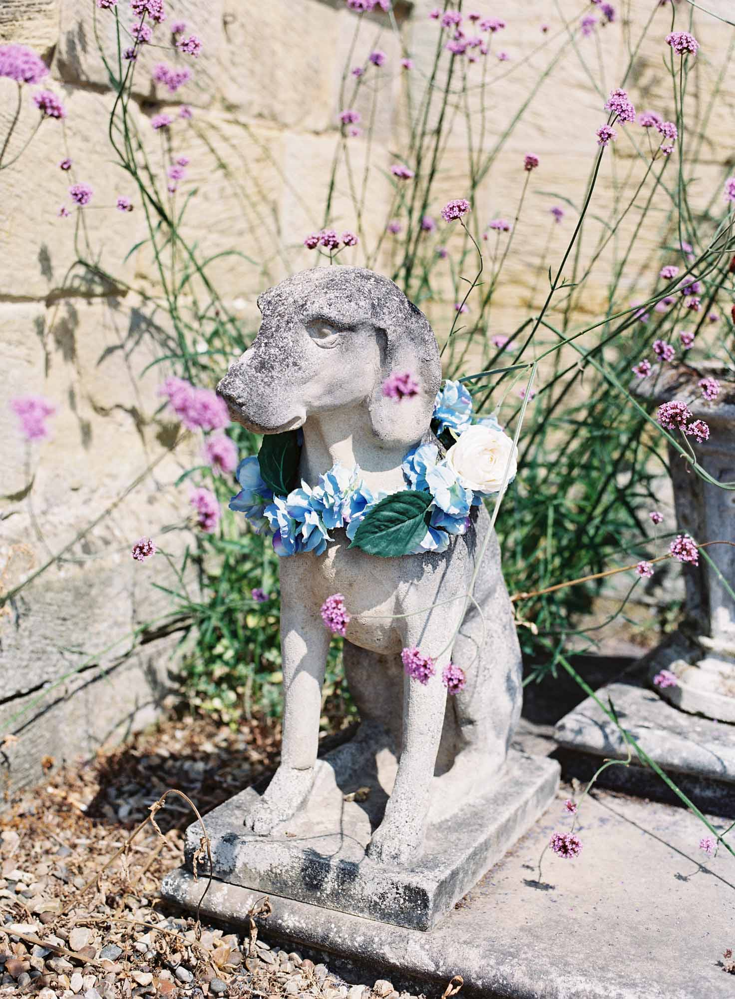 Stone dog at Chiddingstone Castle with flower garland around neck