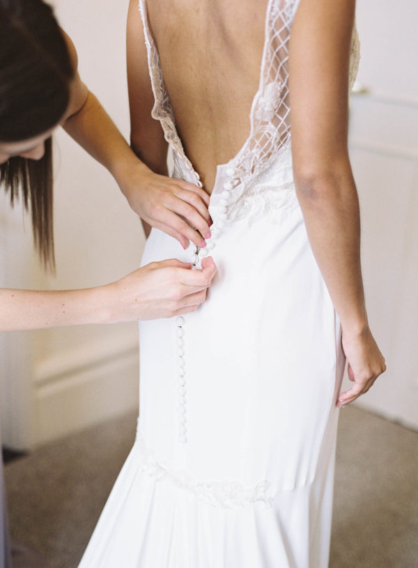 Bride putting on lace Suzanne Neville wedding dress at The Randolph Hotel Oxford