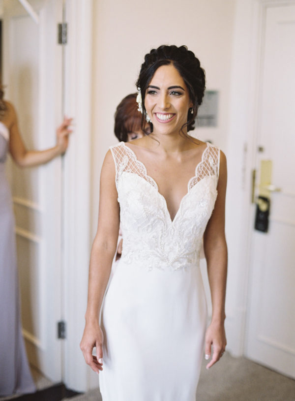 Bride smiling happily in her wedding dress by Suzanne Neville