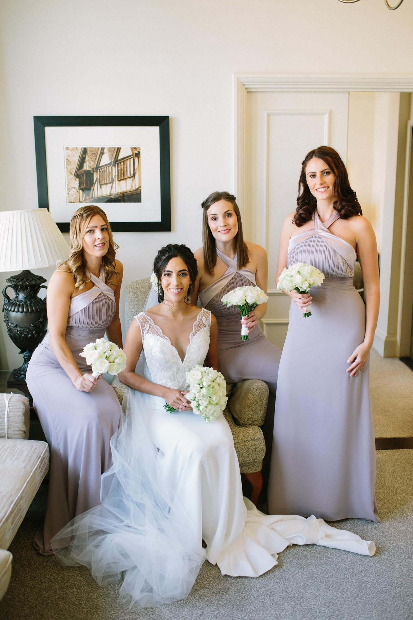 Bride sitting with bridesmaids wearing dusky purple dresses in The Randolph Hotel Oxford