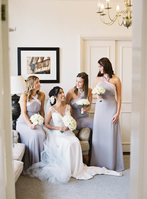 Bridesmaids and bride laughing and smiling at each other in The Randolph Hotel Oxford