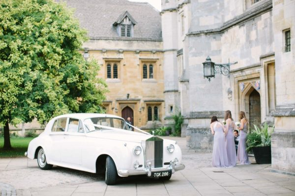 Bridesmaids greeting bride arriving in white vintage wedding car at Magdalen College Oxford