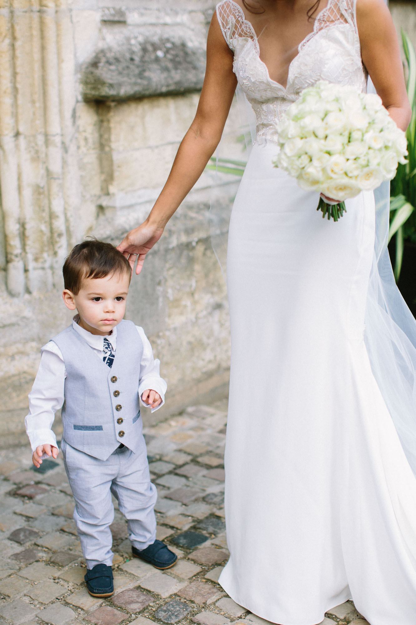 Bride touching page boy's hair outside her Oxford Magdalen College Wedding