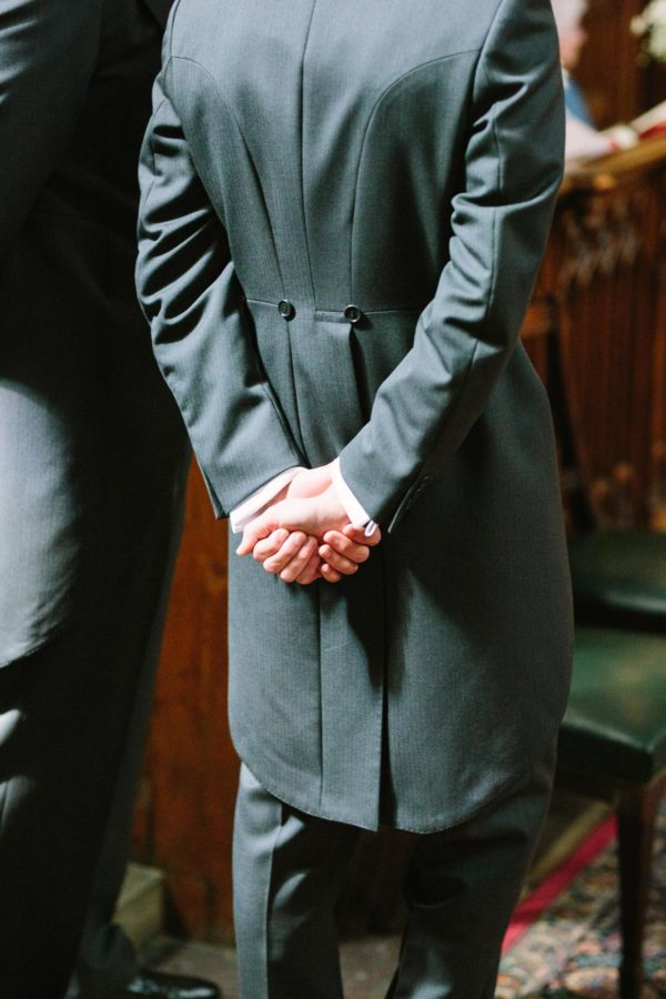 Grooms hands clasped as he waits for his bride in the Magdalen College Chapel Oxford