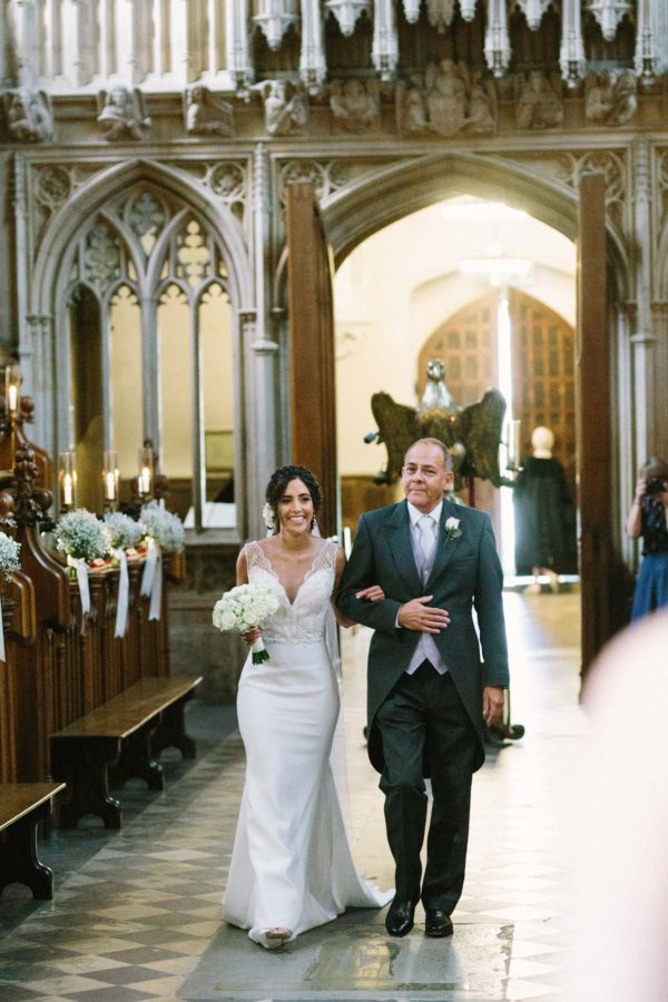 Bride walking into Magdalen Chapel Oxfrord with her father