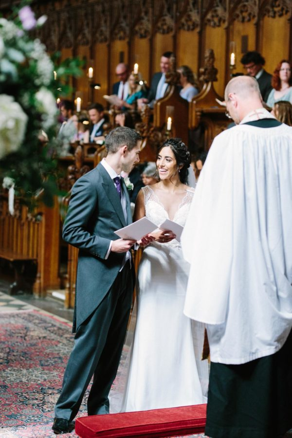 Bride and groom smiling at each other during wedding ceremony at Magdalen College Chapel Oxford