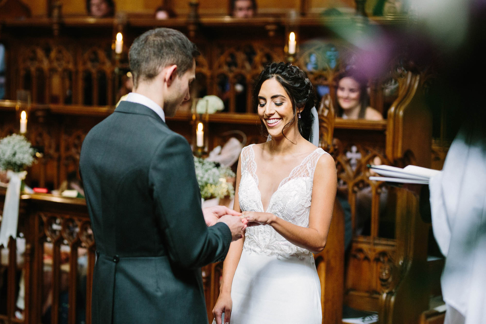 Bride and groom exchanging rings during wedding ceremony in Magdalen College Oxford Chapel