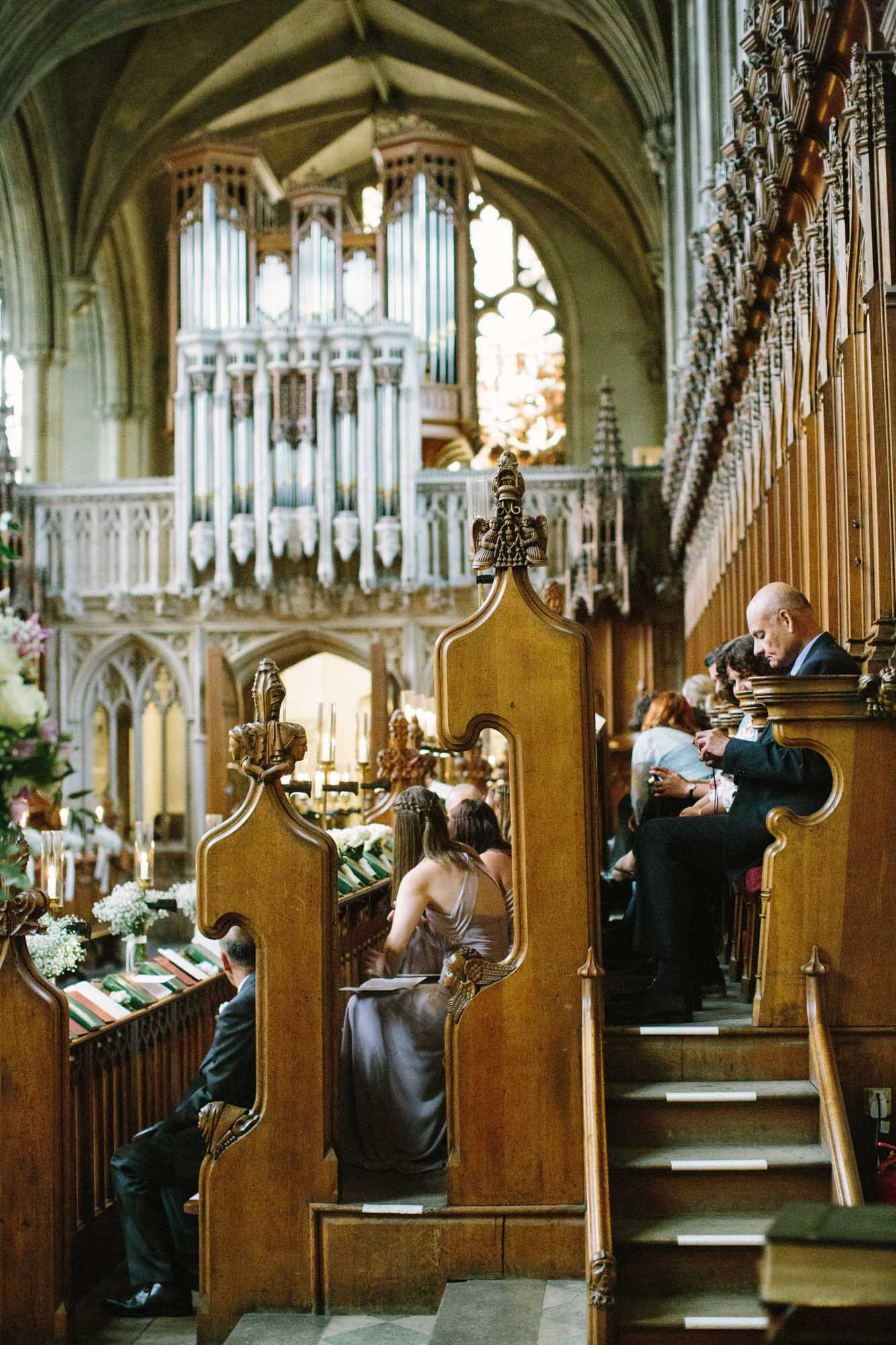 Wedding guests sitting in ornate church pews in Magdalen College Oxford