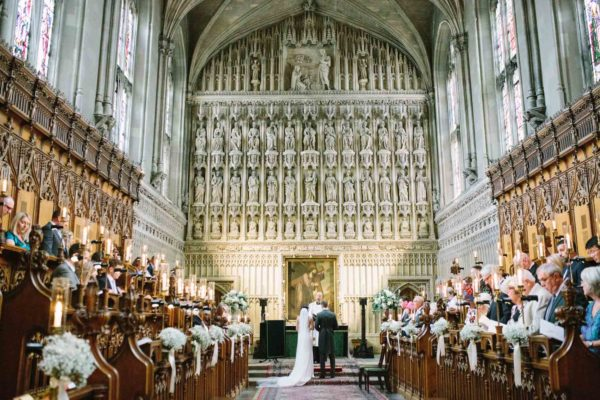 Wide view of bride and groom standing at the alter in the elegant chapel at Magdalen College Oxford