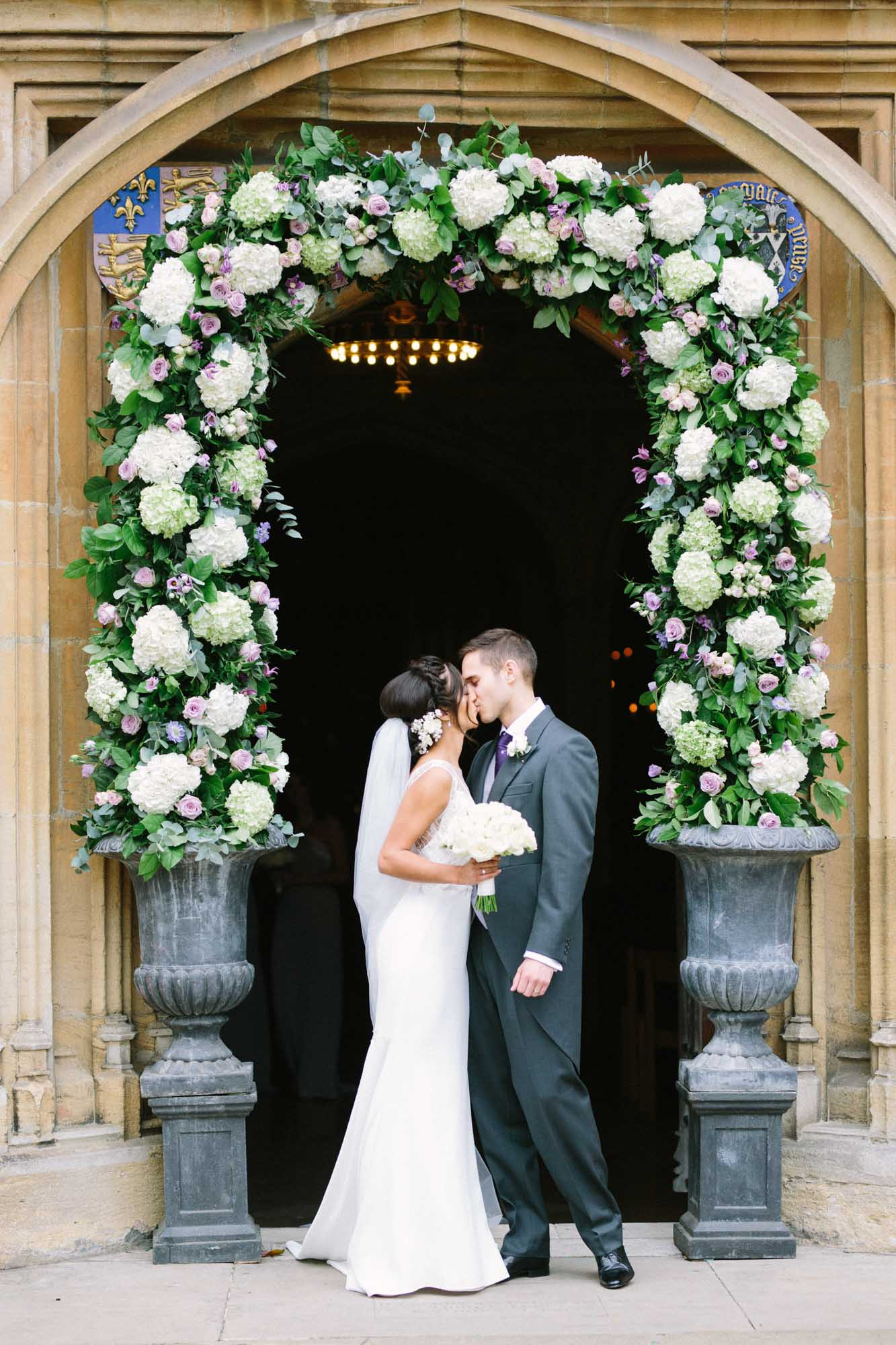 Bride and groom kissing outside the chapel at Magdalen College Oxford