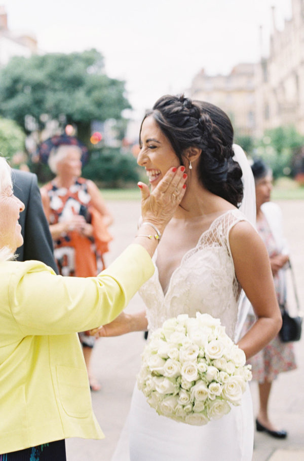 Bride smiling happily as grandmother touches her face by Oxford Wedding Photographer Camilla Arnhold