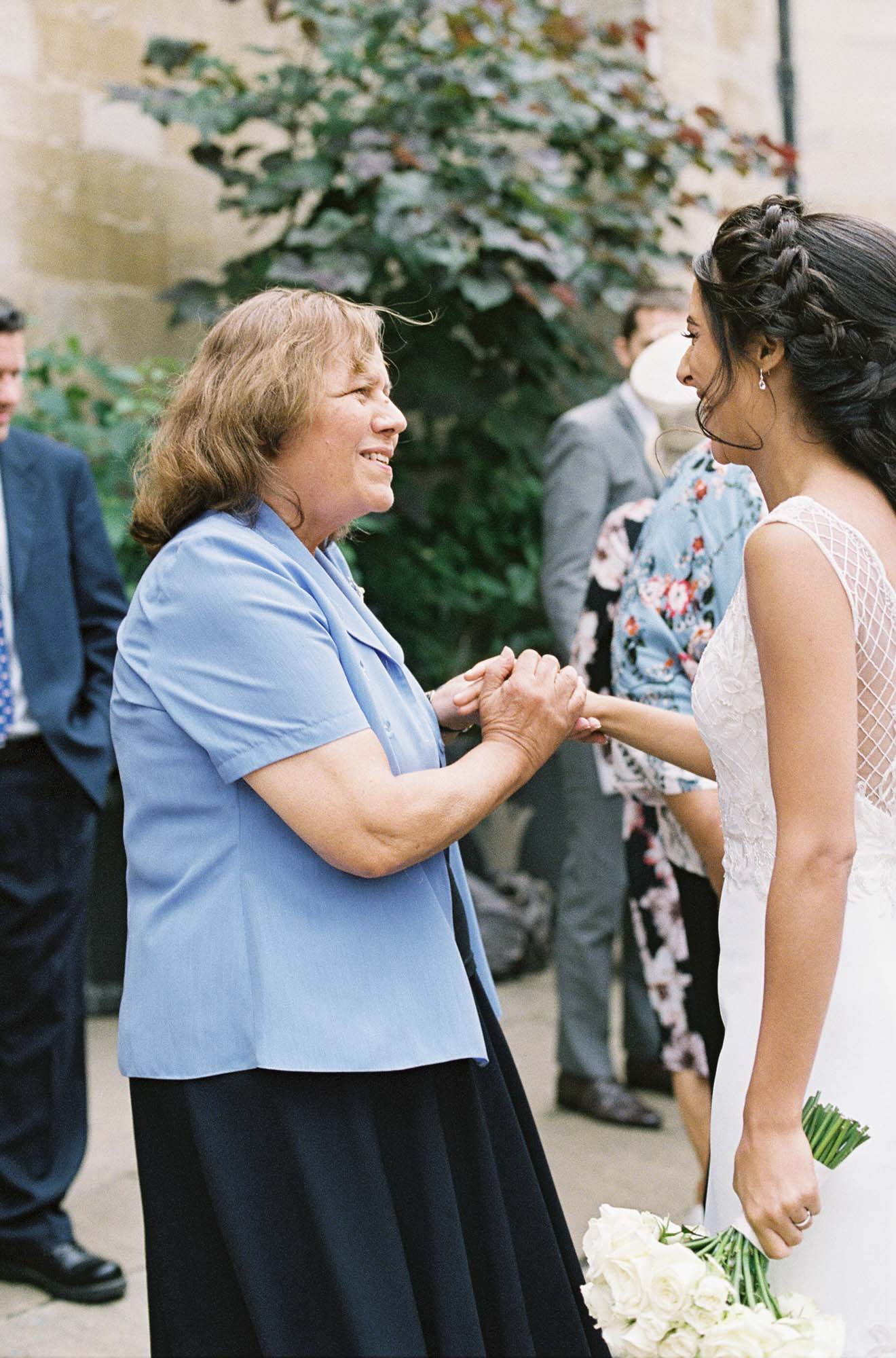 Wedding guests congratulating bride and holding her hand
