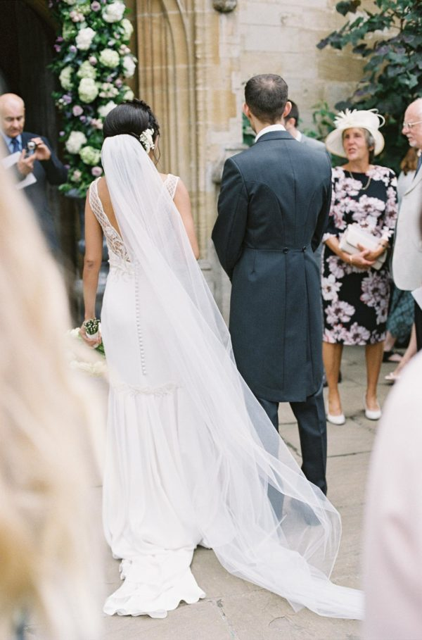 Back view of bride and groom standing outside Magdalen College Oxford